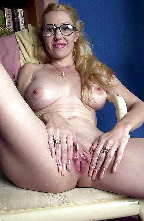 Foxy mature lady in glasses getting naked and playing with a vibrator